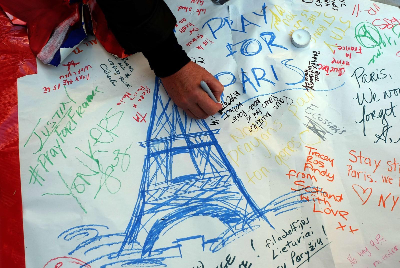 Flere mennesker bidrar til en tegning under minnesmarkeringen i New York.