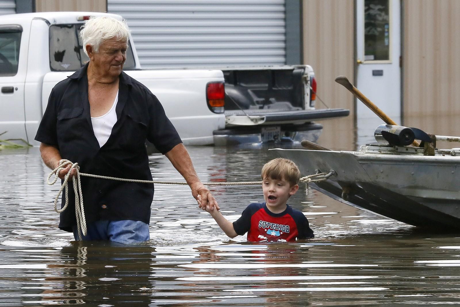RAMMET: Richard Rossi og hans 4 år gamle barnebarn Justice prøver å komme seg gjennom flomvannet etter at hjemmet begynte å ta inn vann i St. Amant, Louisiana.