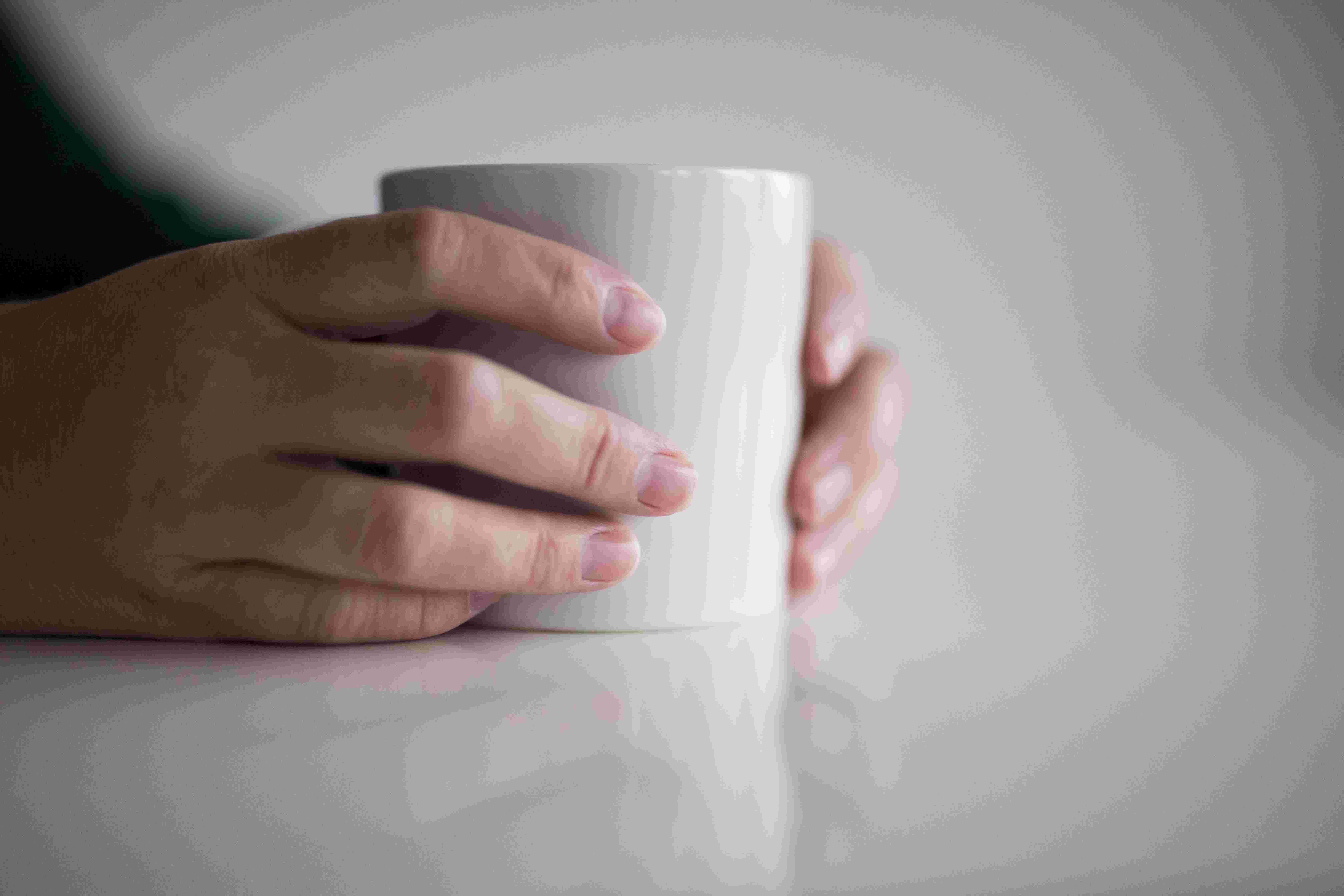 Hender holder rundt kaffekopp