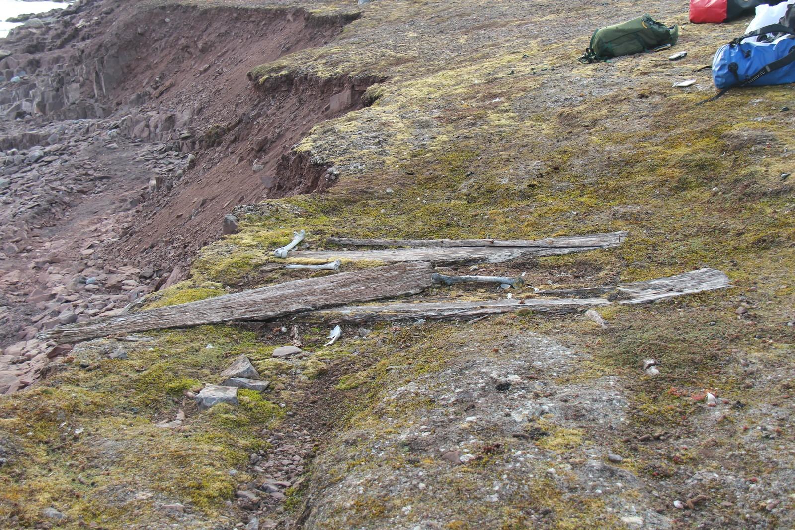 Restene av ei kiste med levninger er presset opp til overflaten ved Reinsdyrflya på Svalbard på grunn av klimaendringer og erosjon.
