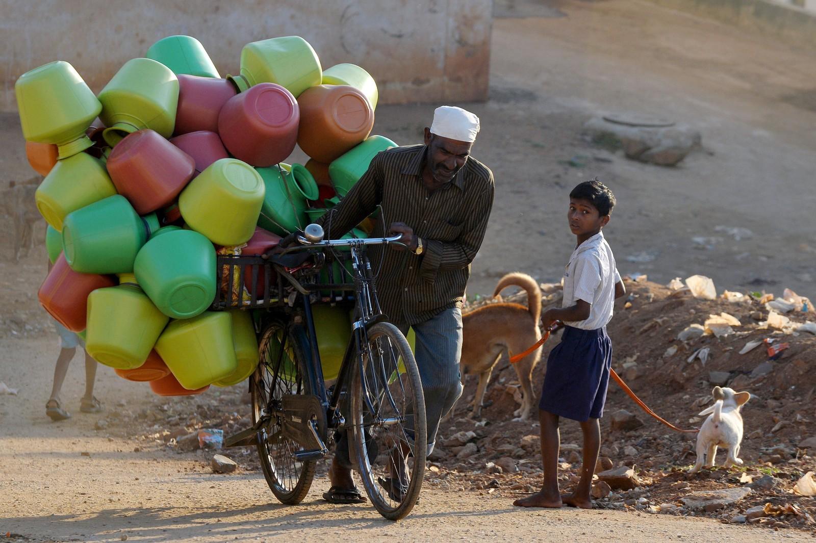 En indisk mann har lastet sykkelen med vanntanker han skal selge i butikken sin.