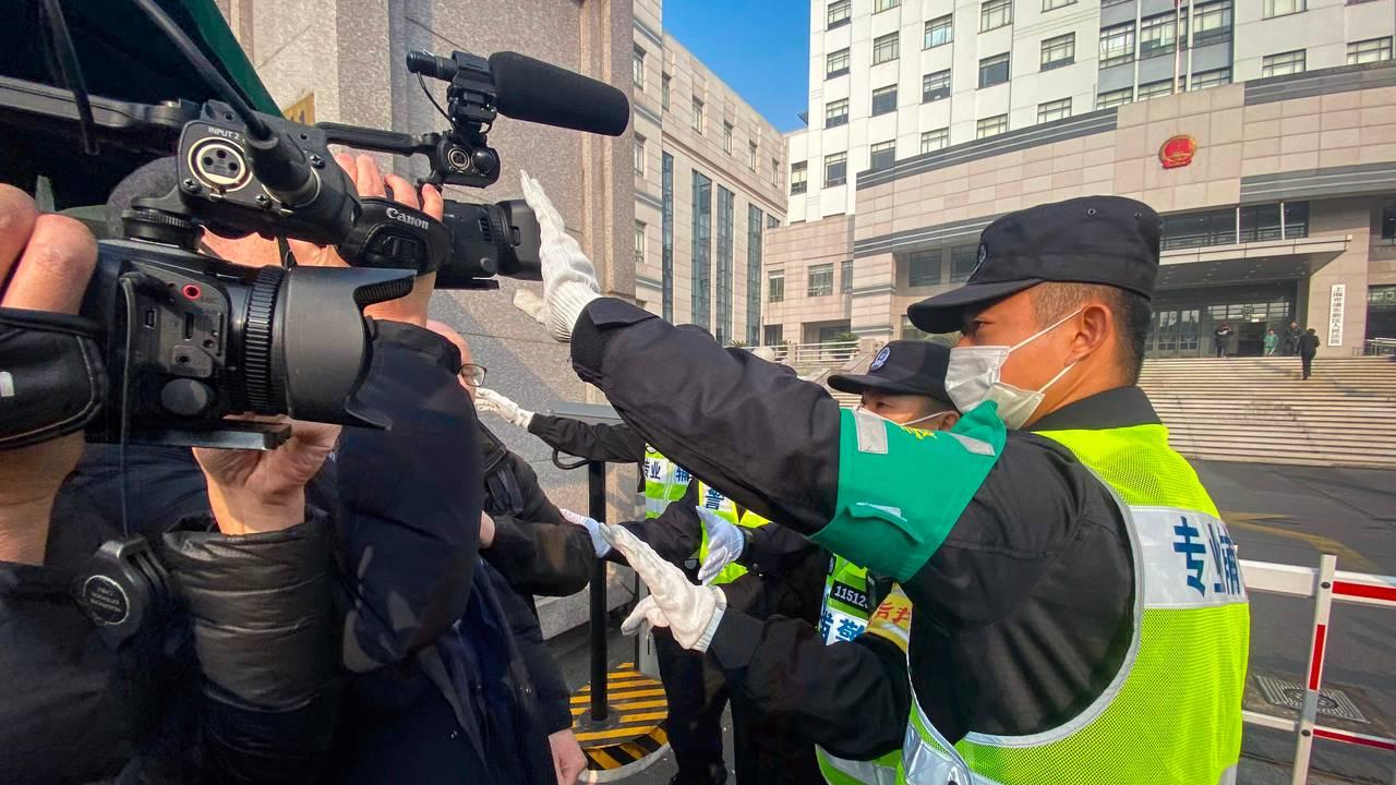 Kinesisk politi hindrer journalister fra å filme utenfor rettsbygningen hvor Zhang Zhan ble dømt til fire år i fengsel, 29. desember.