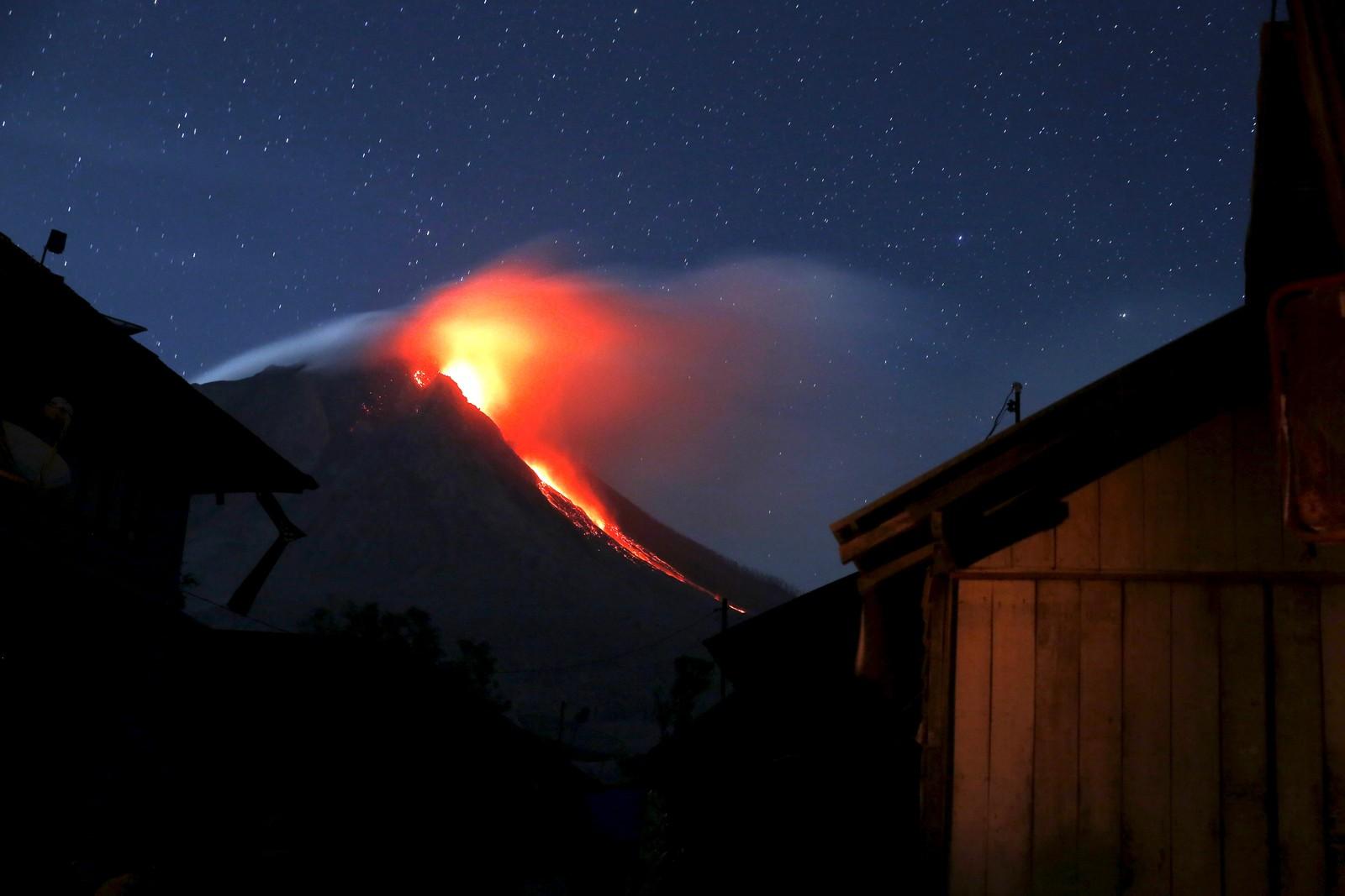 Vulkanen Mount Sinabung i Indonesia spyr lava. I forgrunnen kan man se den evakuerte byen Beras Tepu, som ligger i faresonen. Bildet er tatt 21. juni.