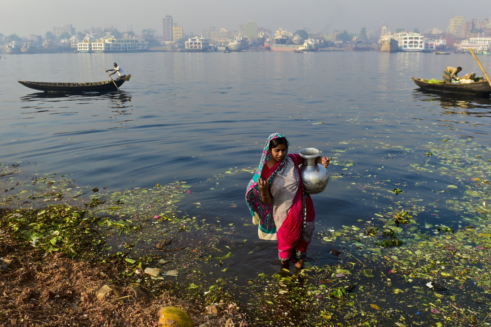 En kvinne fra Bangladesh henter forurenset vann hun skal bruke til å vanne grønnsakene sine.