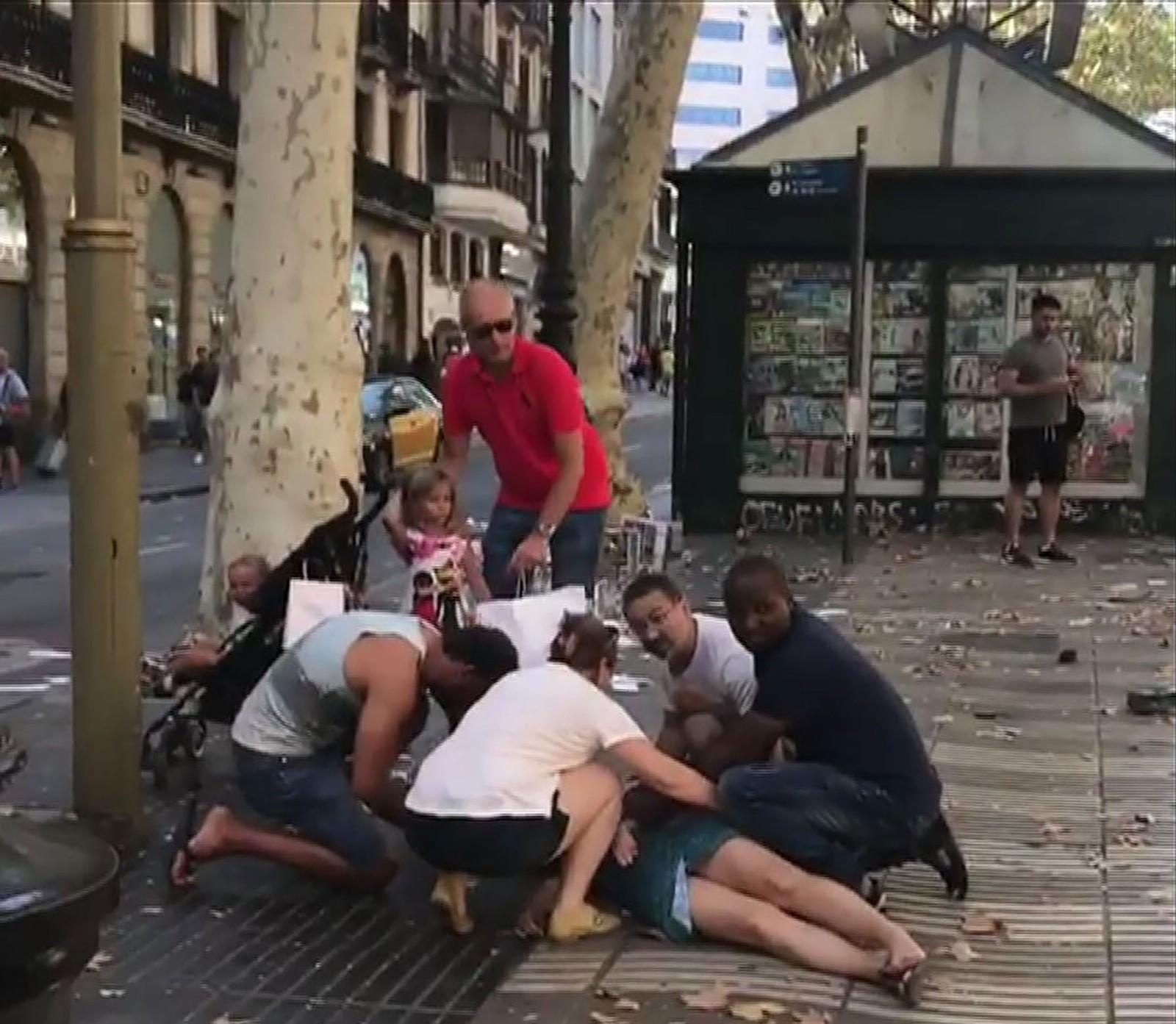 SKADD: Flere personer hjelper en kvinne som ble skadd i terrorangrepet.