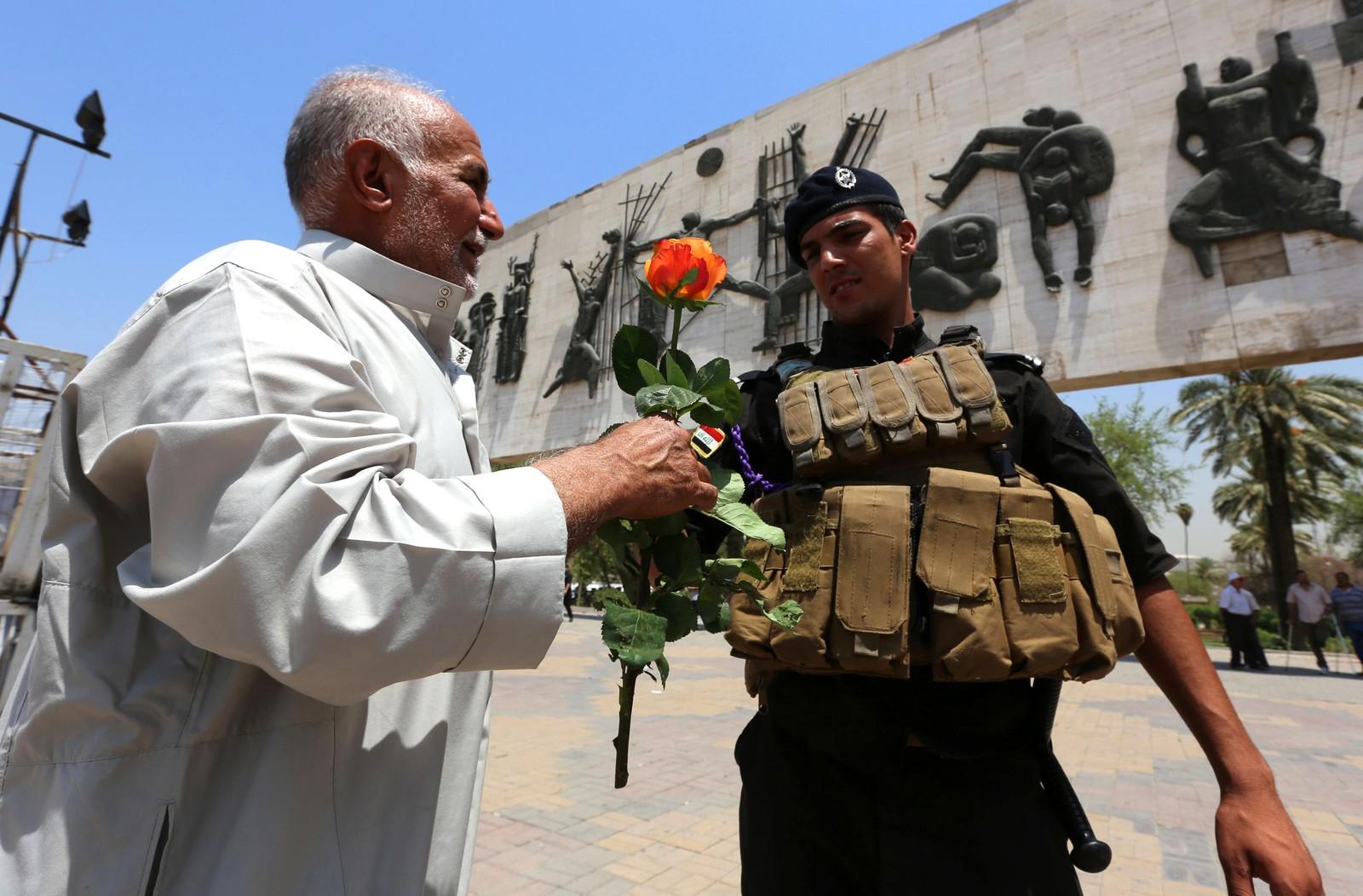 En mann gir en rose til et medlem av de irakiske sikkerhetsstyrkene på Tahrir-plassen i Bagdad den 3. august. Det var en markering denne dagen hvor folk hang opp plakater med budskap om solidaritet fra Nice og andre europeiske byer som har blitt rammet av terrorisme i sommer. Det var en måned siden en bombe drepte 323 mennesker i Bagdad.