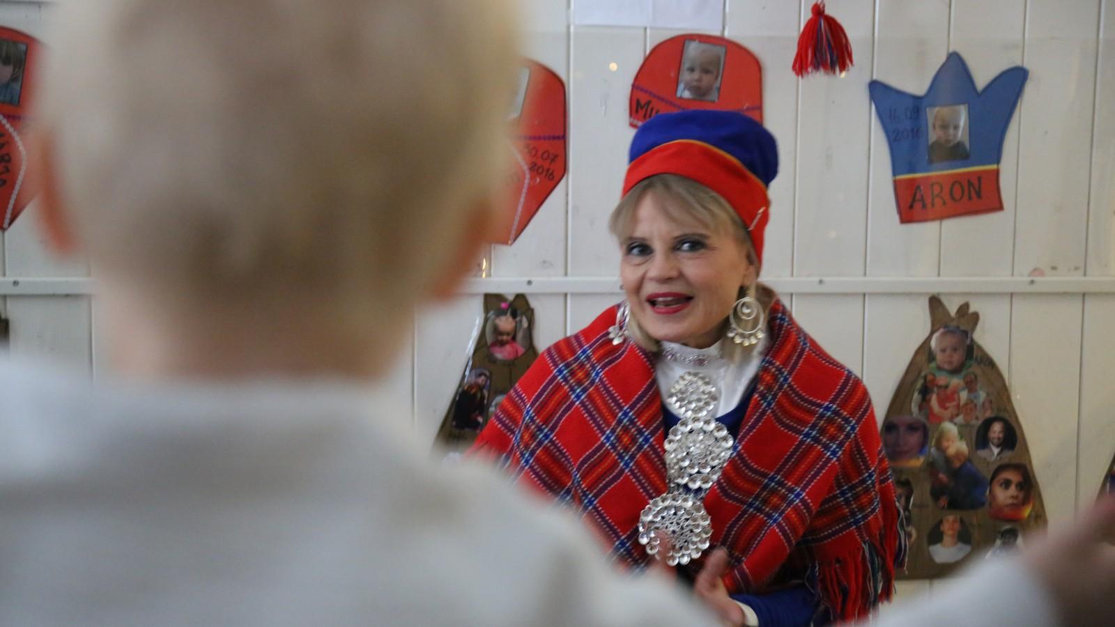 Kvinne i samedrakt i samisk barnehage i Oslo forteller historier til barna. Man ser ryggen av et barn i bildet.