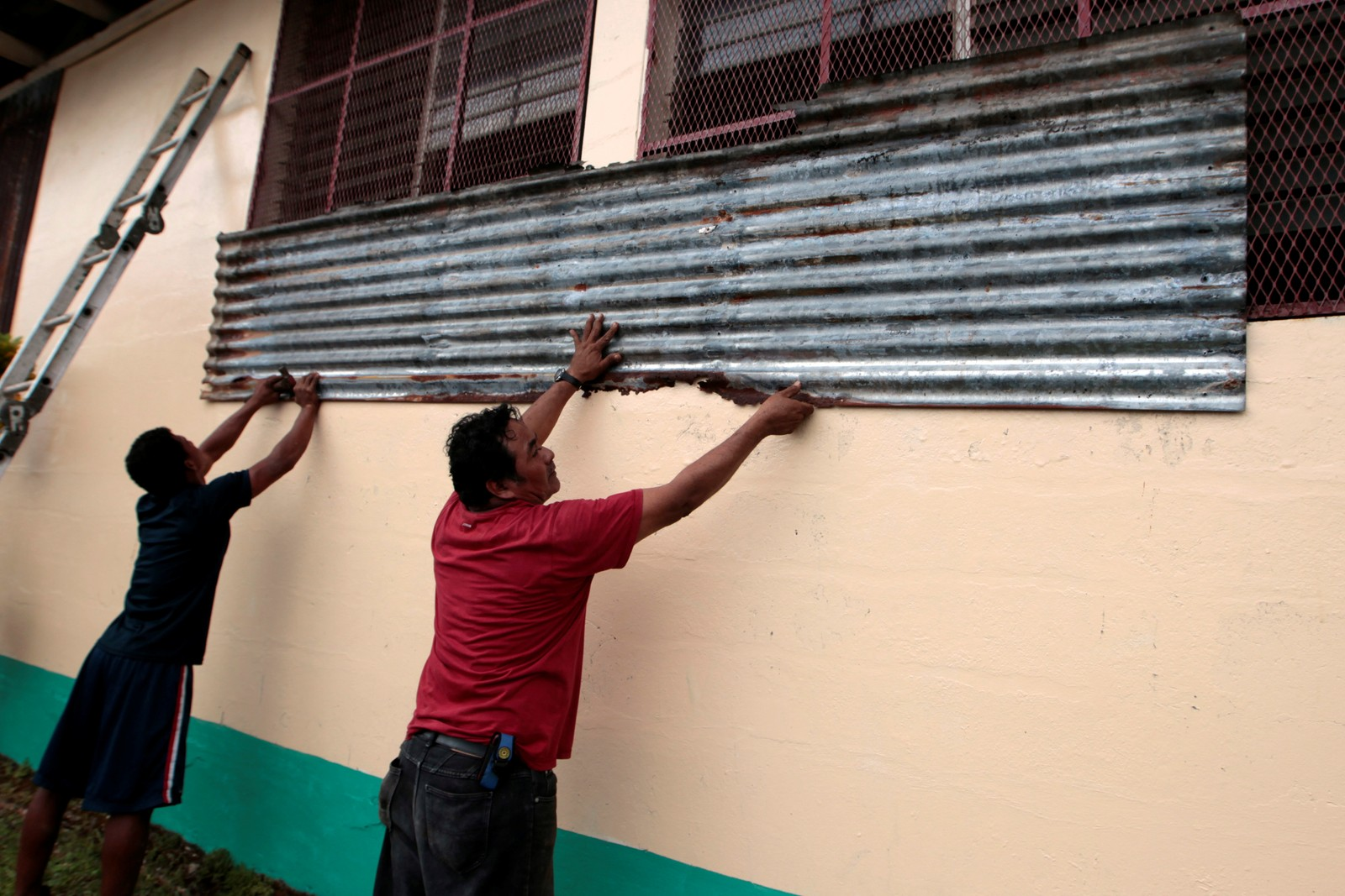 Folk i Bluefields i Nicaragua spikrar igjen vindauga på husa sine med bølgeblekk før orkanen treff land.
