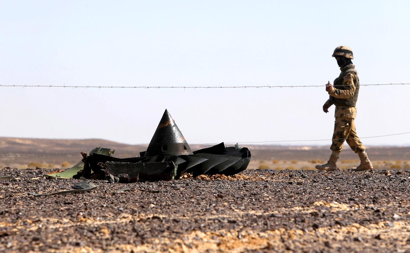 En egyptisk soldat holder vakt i nærheten av det russiske flyvraket. Ved siden av han ligger deler av en motor.