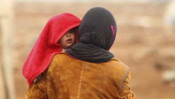 MIDEAST-CRISIS/SYRIA An Internally displaced Syrian woman carries a baby inside a refugee camp in the Hama countryside, Syria