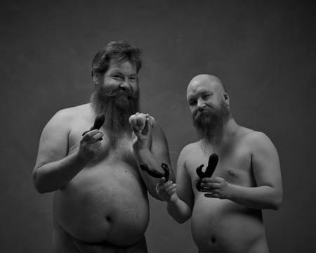 To menn med skjegg står nakne og holder opp sexleketøy. Han ene er kraftig bygd med stor mage. Han andre er skallet. Begge smiler.