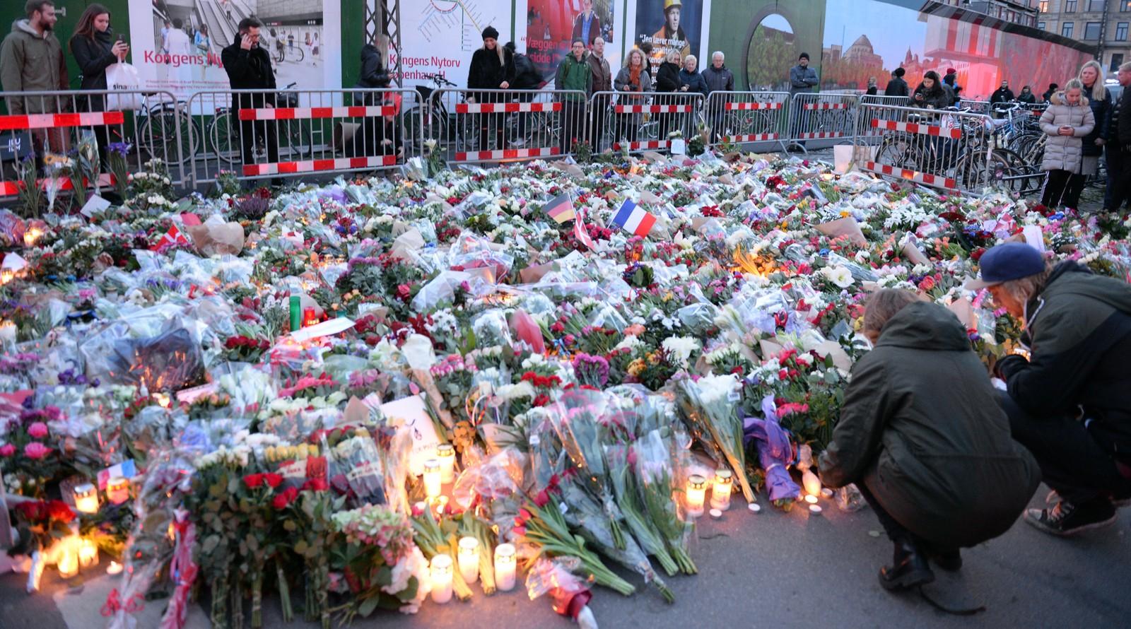 Dansker legger ned blomster ved den franske ambassaden i København.