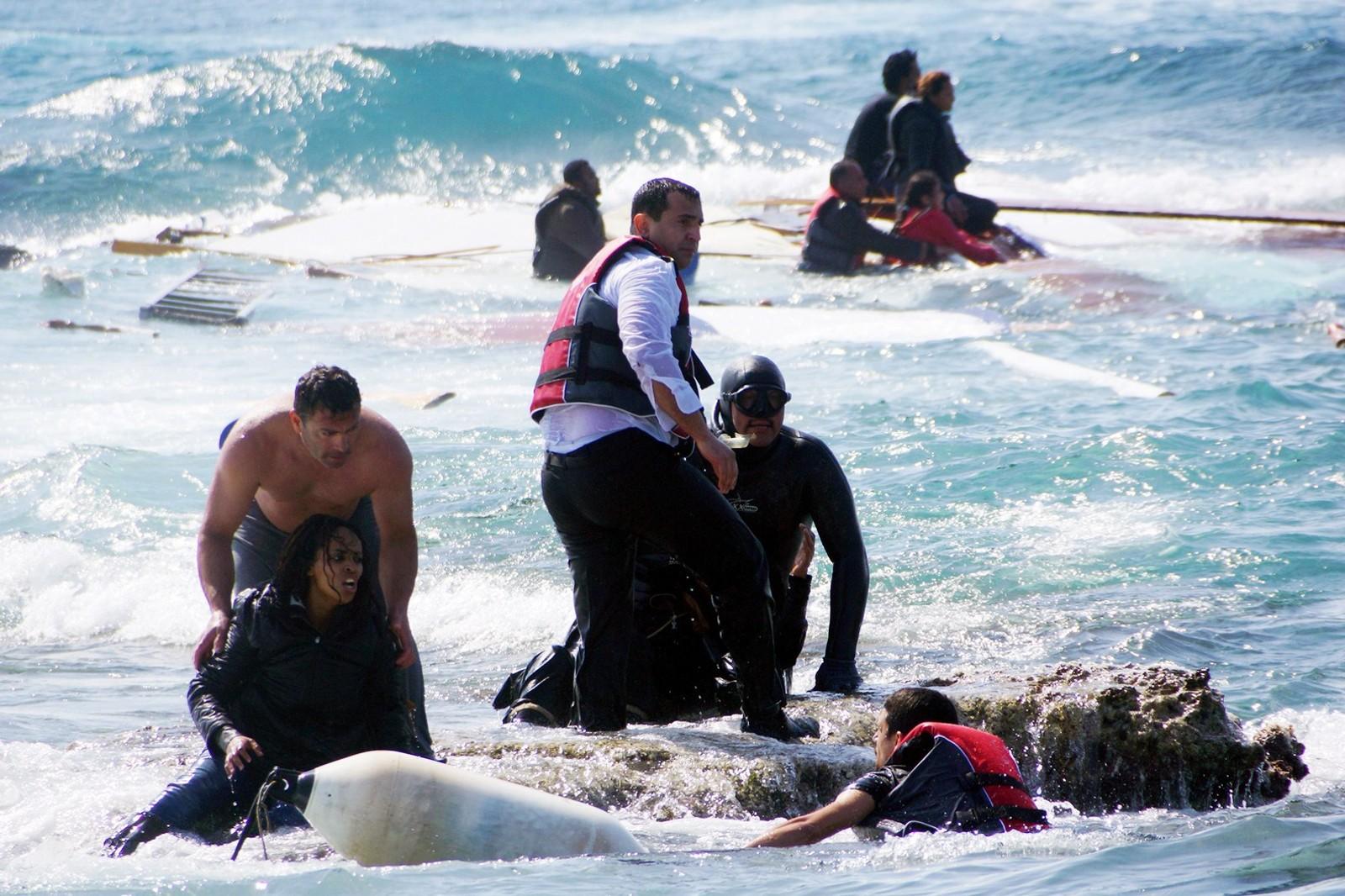 Redningsmannskaper utenfor den greske øya Rhodos hjelper de overlevende i land.