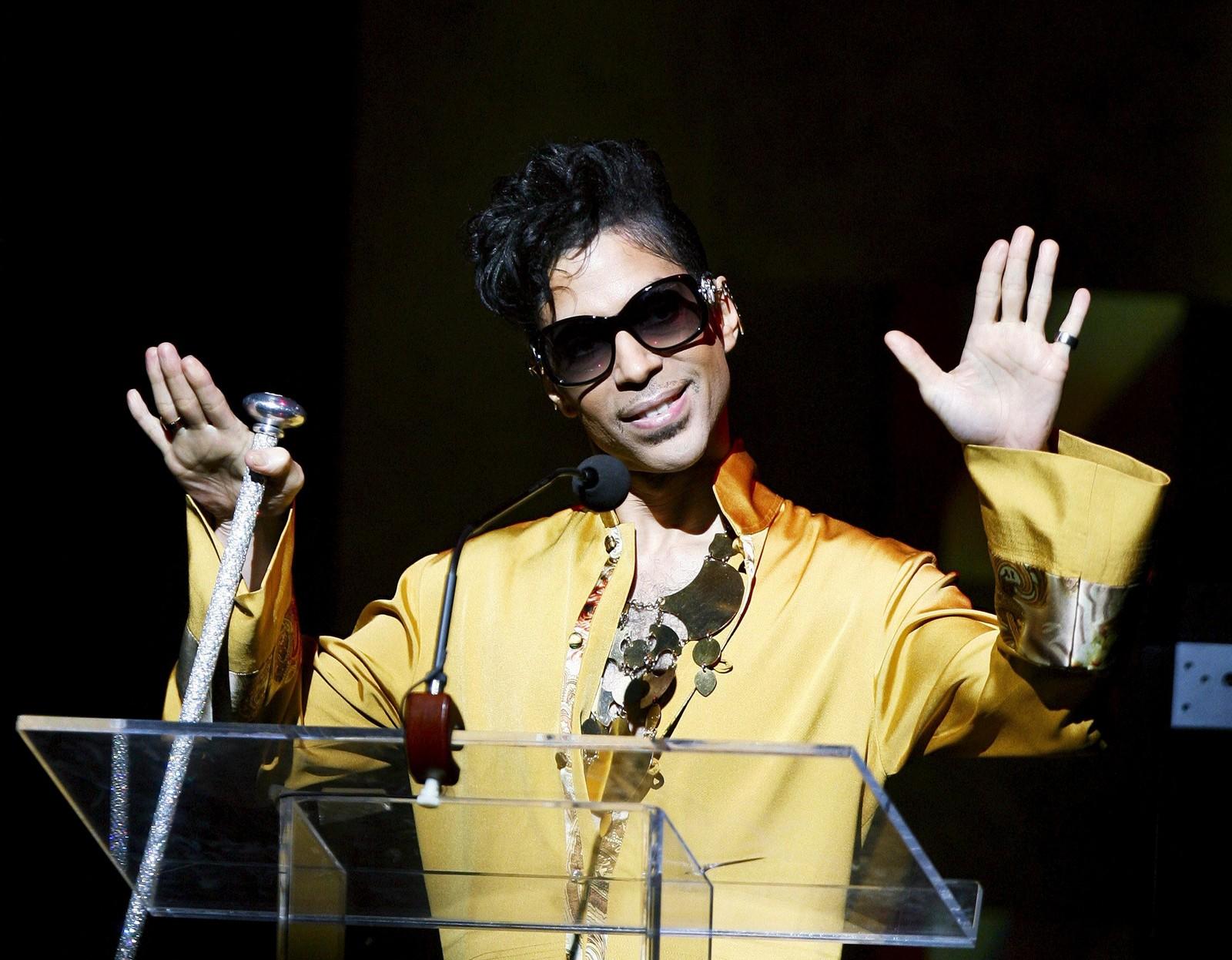 Prince gestikulerer fra scenen på Apollo Theater i New York. Anledningen var den 75. gallaen i 2009.