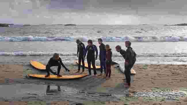 Surfelærer instruerer på stranda.