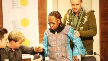 Kian Egan i Westlife hjelper afrikanske Amadou før pressekonferansen til Nobelkonserten.