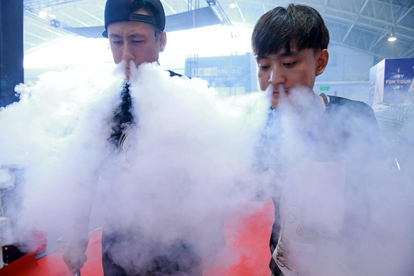 Slik skal de prøve å selge flere elektroniske sigaretter. De to selgerne røyket seg gjennom messedagen i China International Exhibition Center i Beijing torsdag.