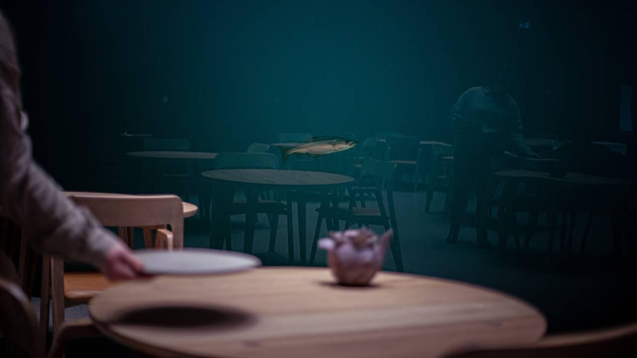 En enslig lyr svømmer utenfor vinduet på undervannsrestauranten Under. I forgrunnen ses en hånd som dekker på bordet.