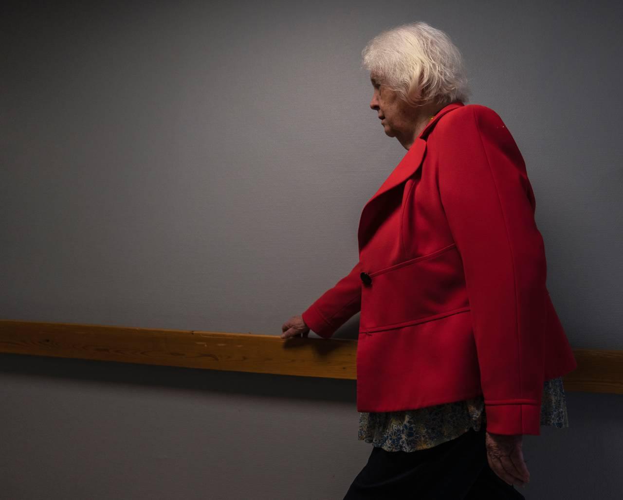 Kvinne i rød jakke går bestemt ned en korridor. Holder seg til gelenderet.