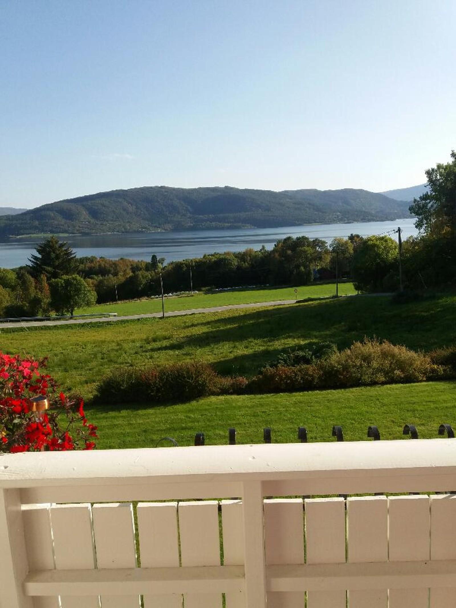 Frå verandaen på Bjerkestrand med utsikt mot Freifjorden. Ikkje ei sky på himmelen.