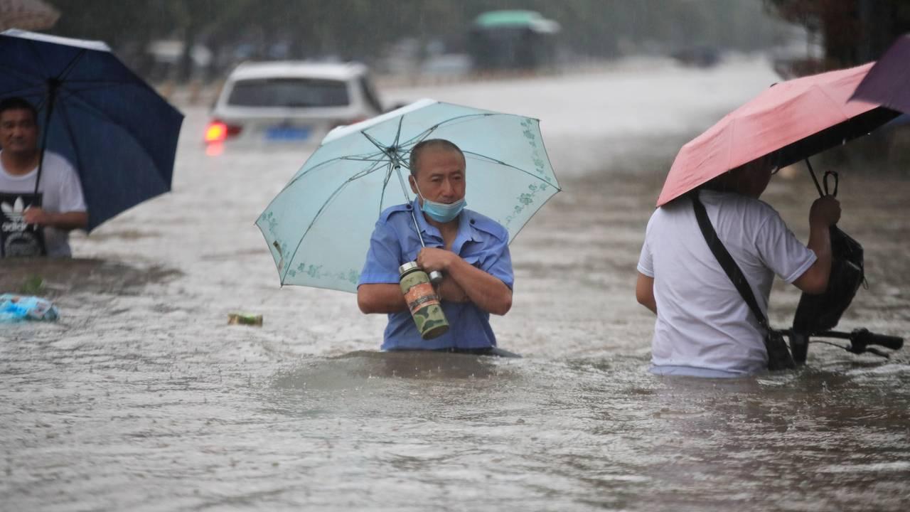 En mann vasser gjennom flomvann etter kraftig nedbør i byen Zhengzhou.