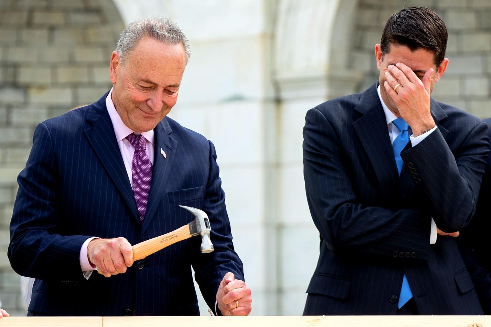 Leder av Representantenes hus, Paul Ryan til høyre, klarer ikke å unngå å le. Senator Charles Schumer bøyer nemlig spikeren. Det var meningen at denne første spikeren skulle være starten på byggingen av plattformen der den neste presidenten skal innsettes i 2017. Bildet er tatt i Washington i USA.