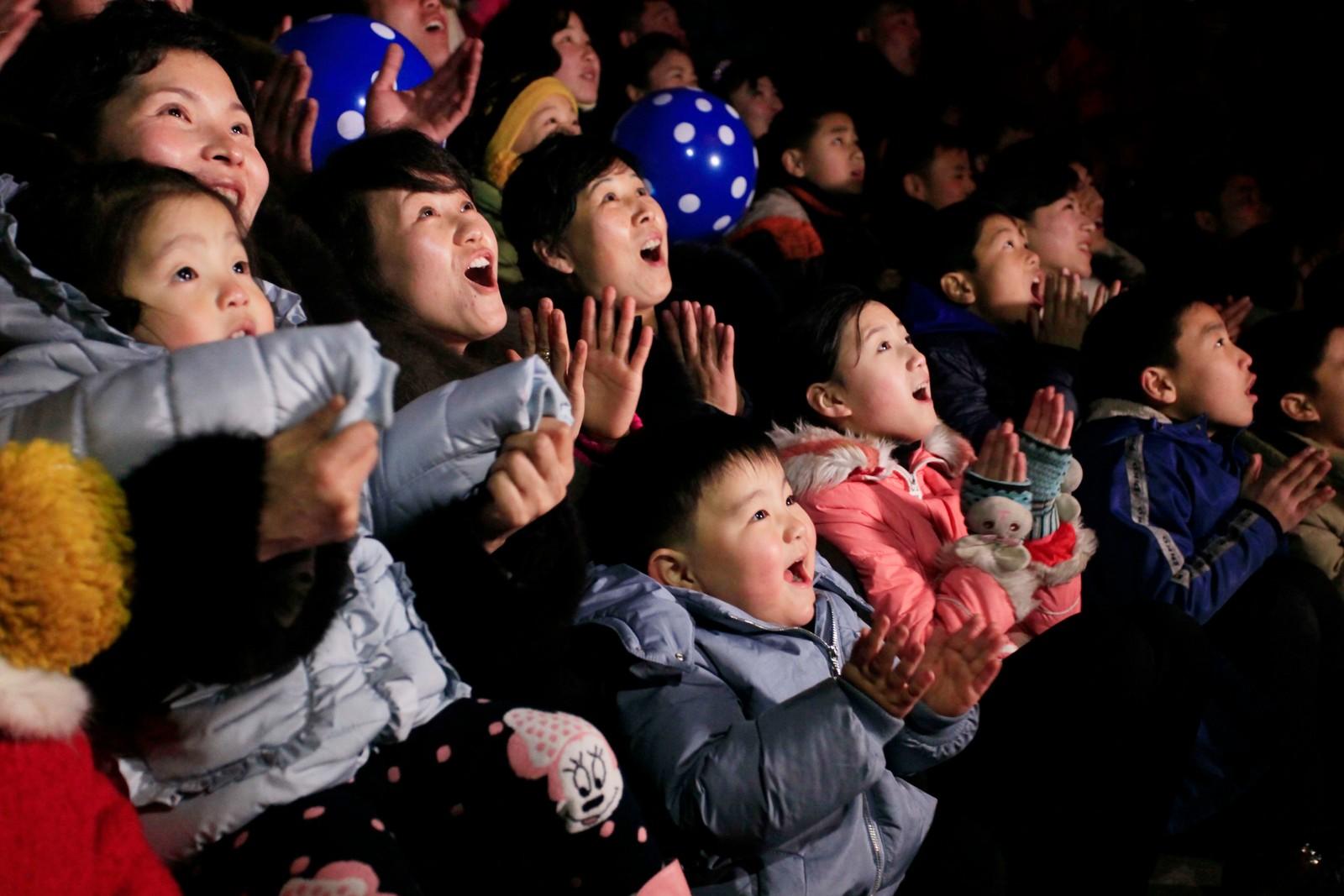 PYONGYANG: Foreldre og barn beundrer nyttårsfyrverkeriet over Kim Il Sung-plassen i Pyongyang i Nord-Korea.