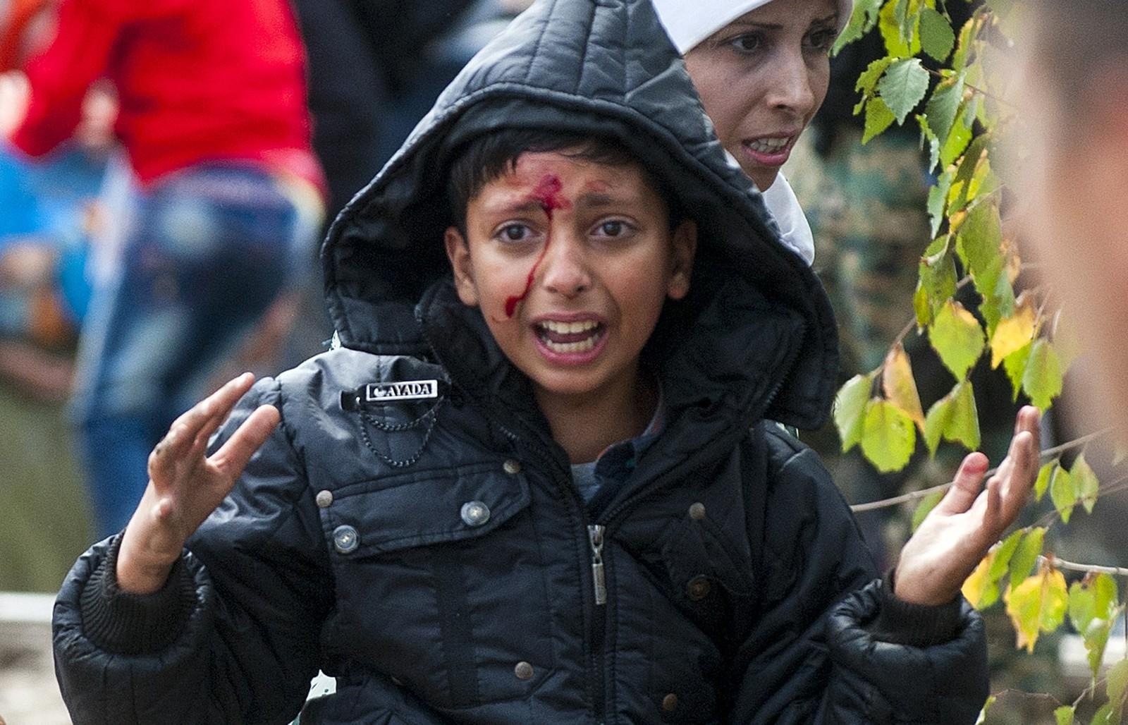 Et fortvilet og skadet barn gråt etter møtet med makedonske grensevakter. Flere tusen prøver å krysse grensa mellom Hellas og Makedonia.