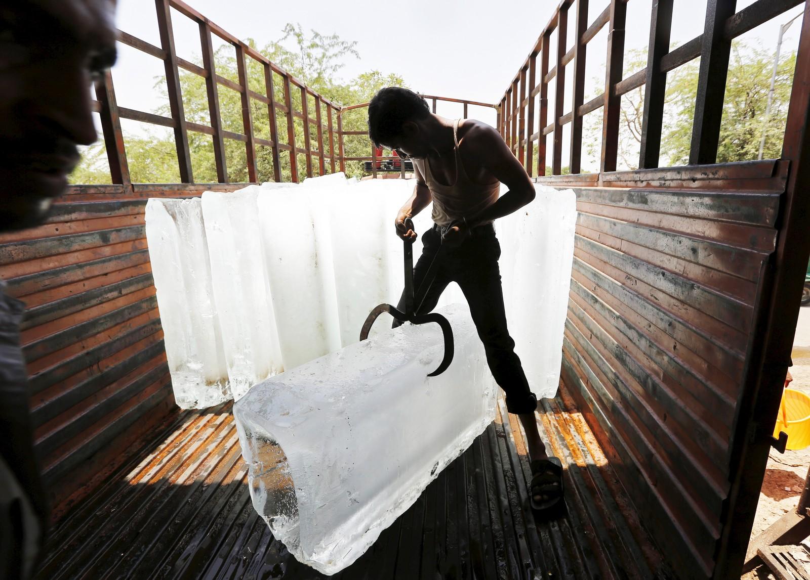 Mann losser isblokker i Ahmedabad i India.
