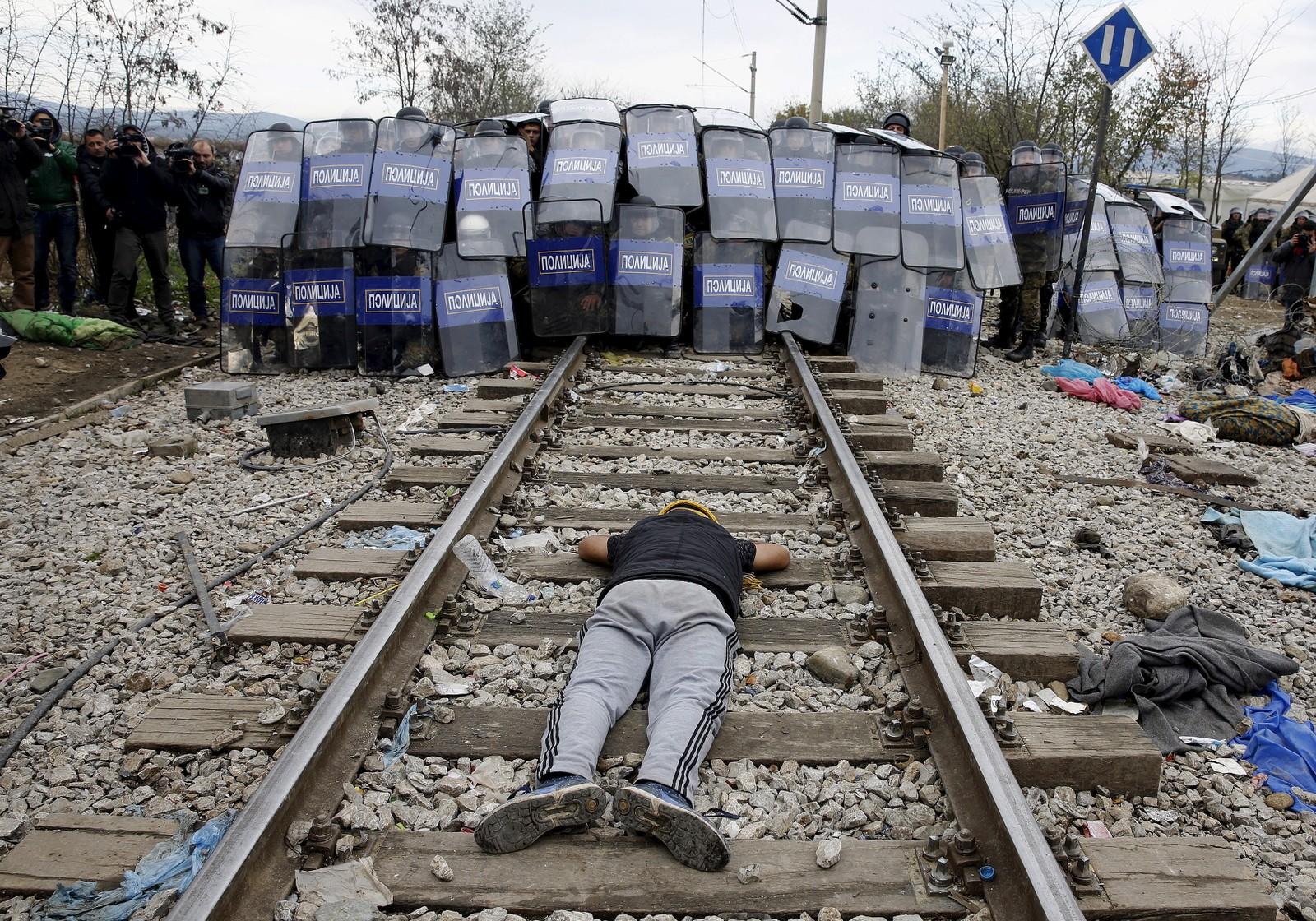 En flyktning fra Iran legger seg foran det makedonske politiet ved grensa mellom Hellas og Makedonia. Opptøyer brøt ut etter at en ung flyktning skal ha dødd av elektrosjokk da han skulle krysse toglinja.