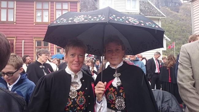 BUNADEN PÅ: Bjørghild Holien og Kristin Evensen i fin Valdres-bunad og med paraply under 17. mai-feiringa i Lærdal.