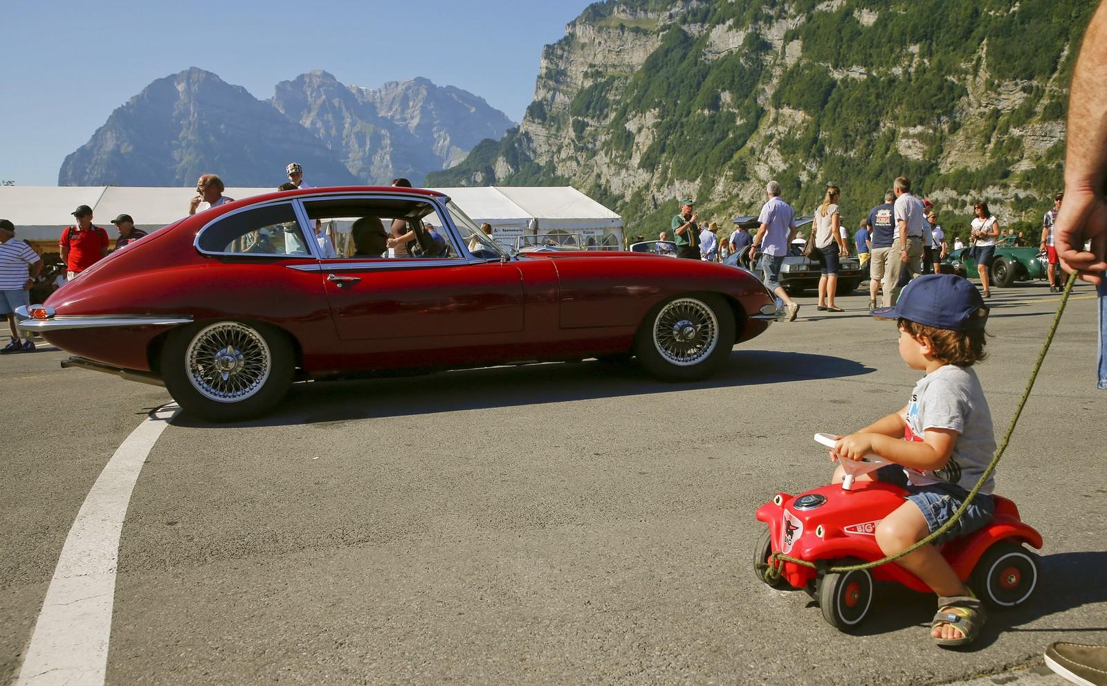 En liten gutt ser (drømmende) mot en Jaguar E-Type sportsbil under British Car Meeting 2015 i Mollis, Sveits. 1300 veteranbileiere var samla der denne uka.