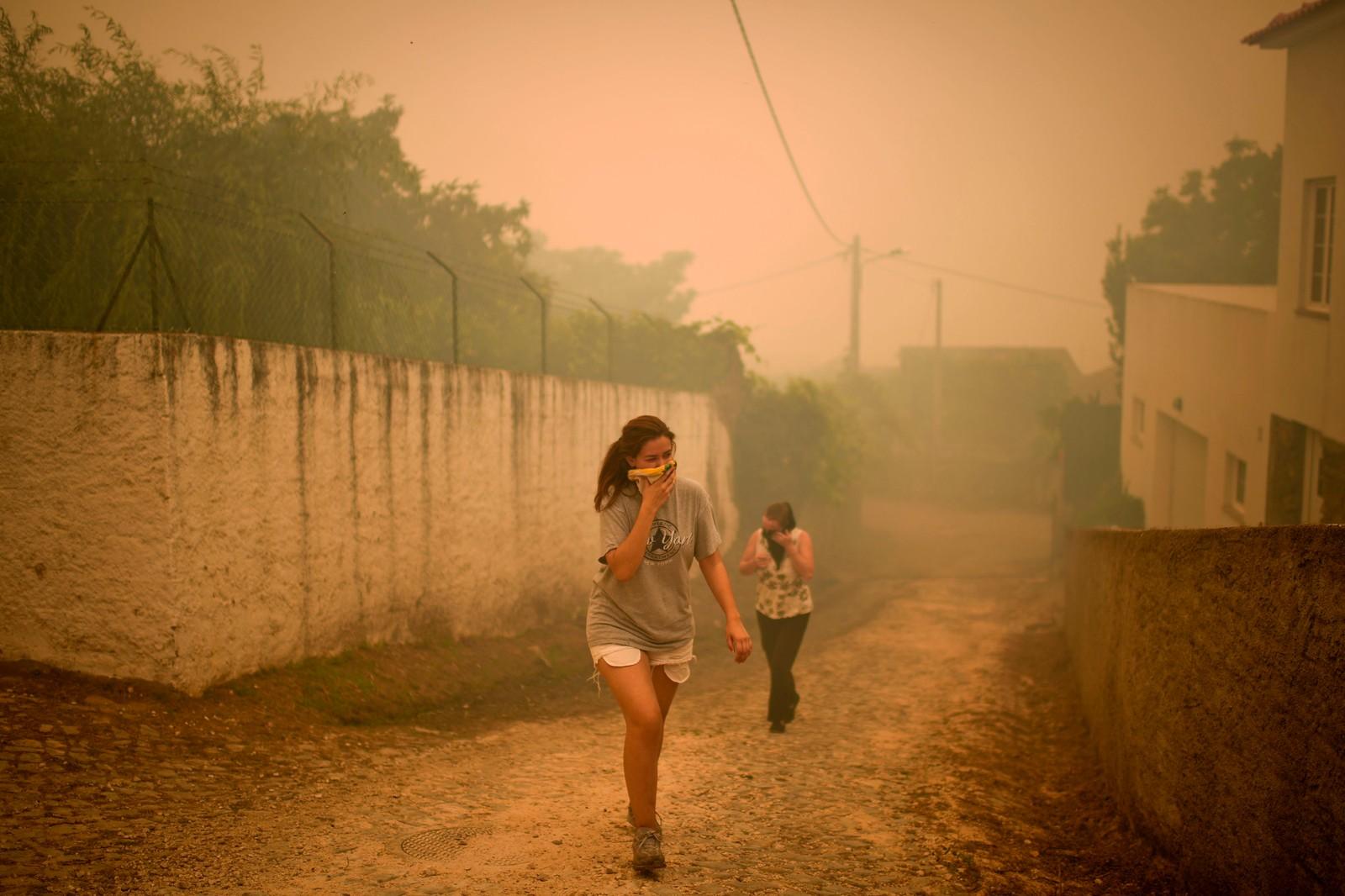 Innbyggere i Torgal i Castanheira de Pera dekker til munn og nese for å beskytte seg fra røyken fra skogbrannen som truer landsbyen.