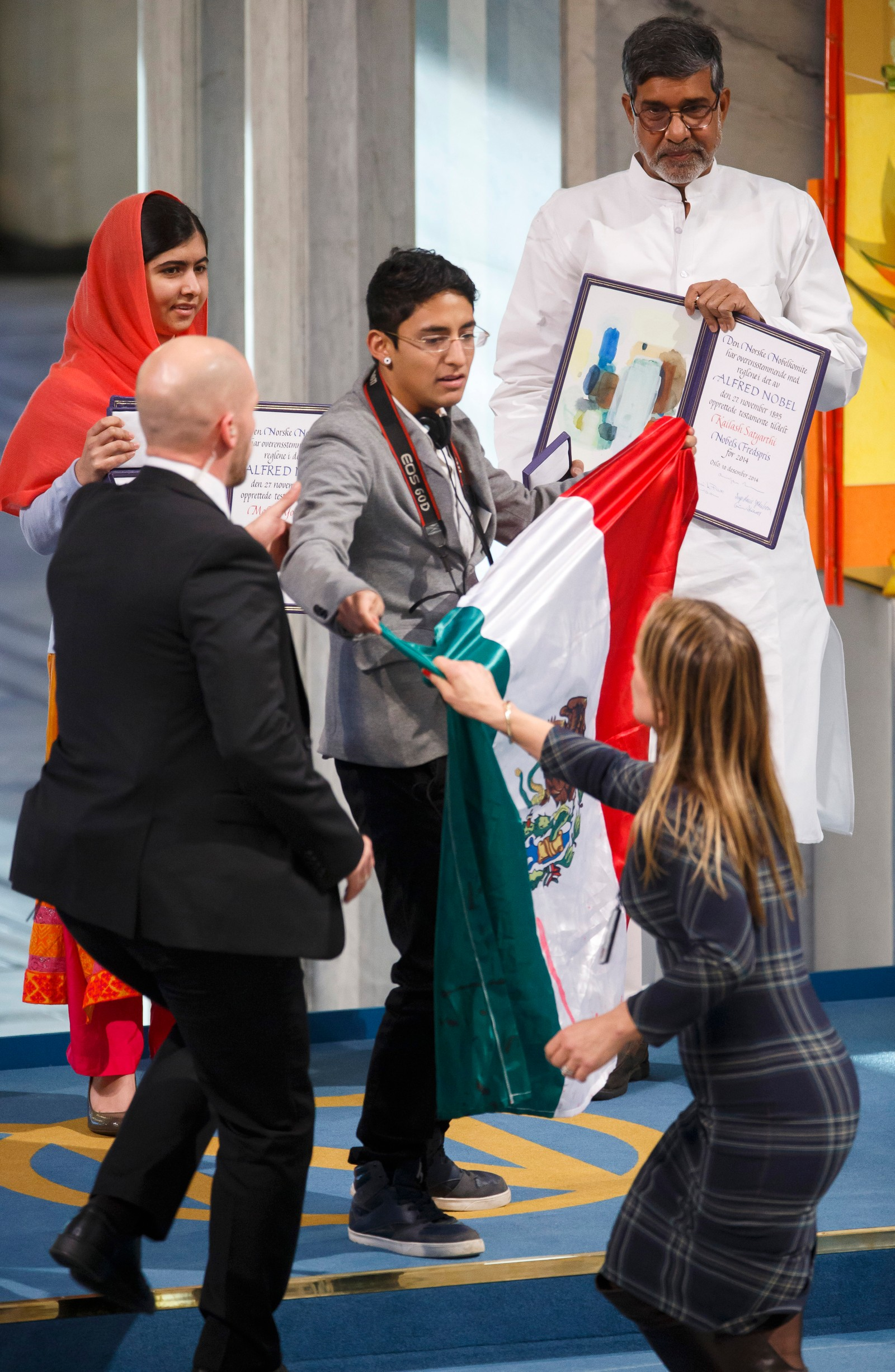 A man holding the Mexican flag is led away by security after attempting to get on stage with Nobel Peace Prize winners Malala Yousafzai from Pakistan and Kailash Satyarthi of India during the Nobel Peace Prize award ceremony in Oslo, Norway, Wednesday, Dec. 10, 2014. The Nobel Peace Prize is being shared between Malala Yousafzai, the 17-year-old Taliban attack survivor, and the youngest Nobel Prize winner ever, and Indian children's rights activist Kailash Satyarthi in a ceremony in Oslo on Wednesday. (