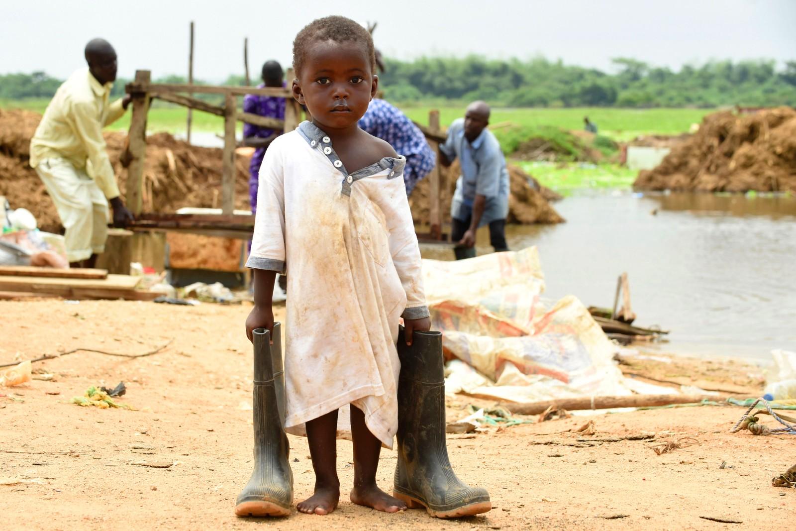 En liten gutt passer på farens støvler etter at hjemmet deres har blitt tatt av flom. Flere tusen er hjemløse i Ogun i Nigeria etter at elven Ogun flommet over.
