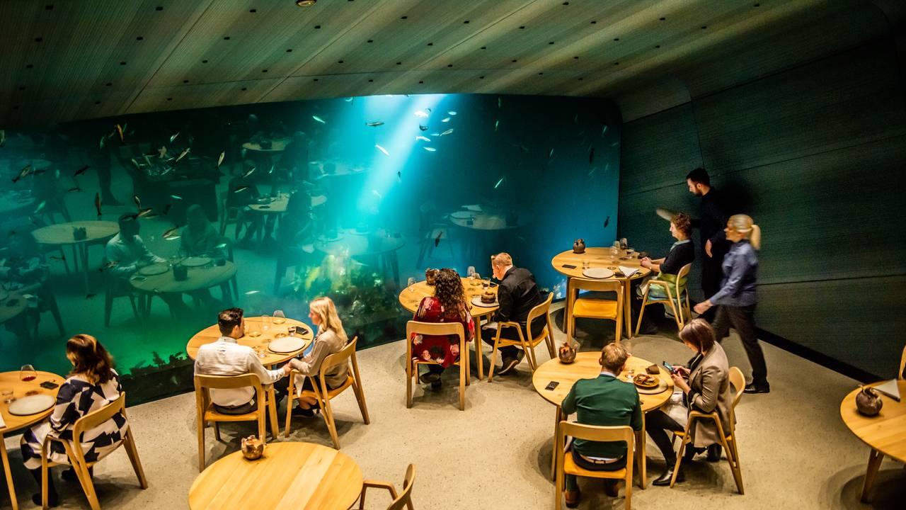 Folk sitter og spiser på Undervannsrestauranten Under mens fisk svømmer utenfor vinduet