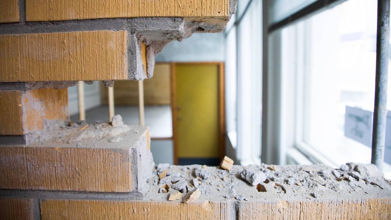 Mursteinsveggen skal rives, og mursteinen skal brukes på nytt. Man ser et hull i veggen der noen få mursteiner er fjernet. Gjennom hullet ser man inn i et rom, der en dør leder inn i enda et rom.