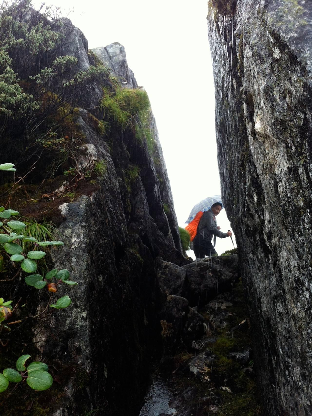 Smal sprekk i fjellpasset, som en døråpning hvor pilgrimsvandreren i Himalaya klatrer med paraply