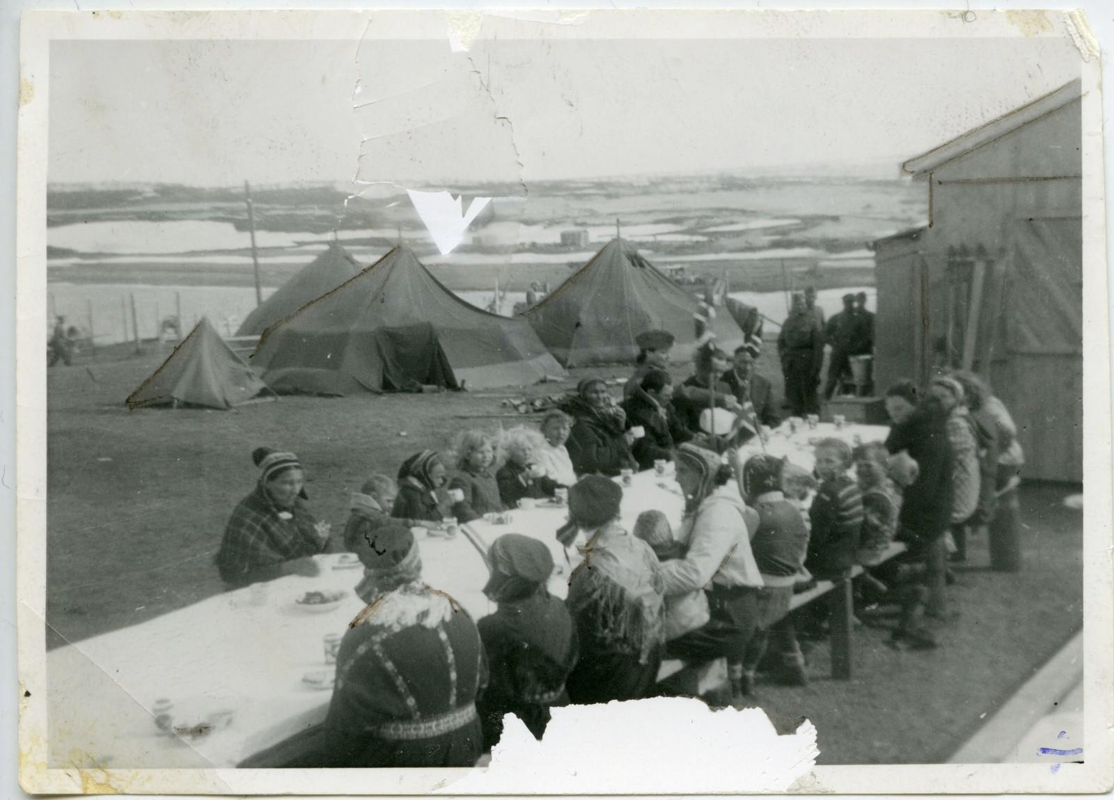 Original bildetekst: Kautokeino 17. mai 1945. Vi stekte vafler, dekket bord ute, kokkene som bor i teltene her, kokte kakao, ellers hadde vi en pakke kjeks, og en plate melkesjokolade til hver.  Gjestene kom og man gikk til bords, barn i alle aldre. Fotografiet kommer fra et album gitt til Riksarkivet av sykepleier Marie Lysnes. Våren 1945 deltok hun i opprettelsen av et feltsykehus i Finnmark. Lysnes dokumenterte oppholdet i Finnmark gjennom tekst og bilder. Almumet er en del av privatarkivet etter Marie Lysnes.