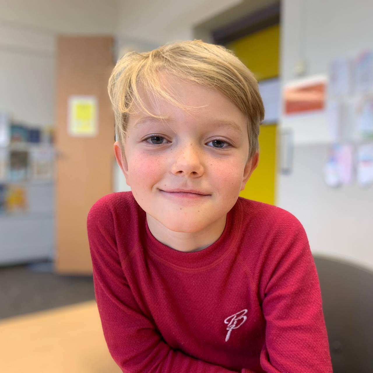 Magnus sitter ved pulten i klasserommet.