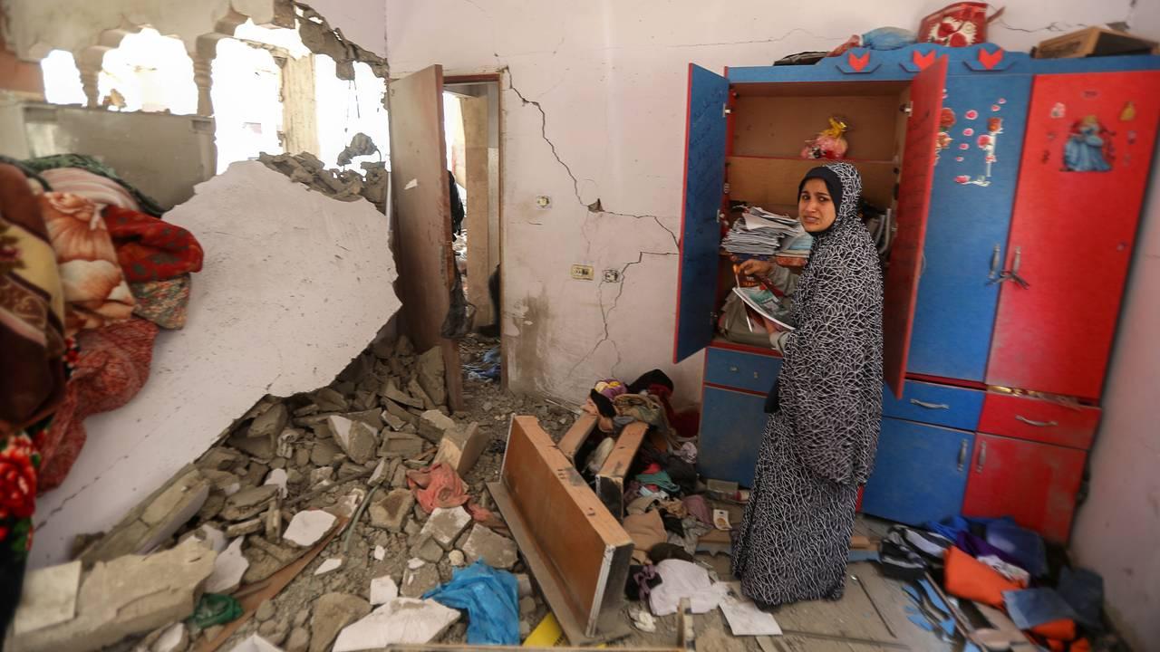 En palestinsk kvinne forsøker å samle sammen tingene sine etter at bygningen leiligheten ligger i ble bombet av israelske luftstyrker natt til fredag.