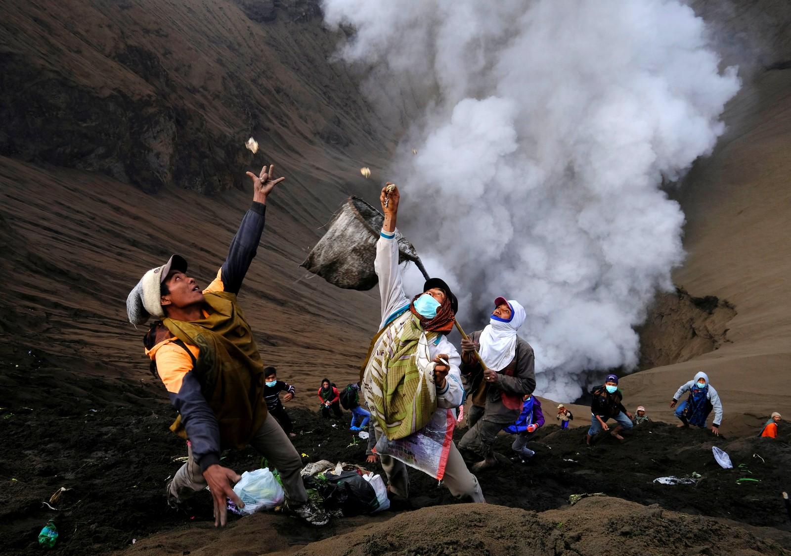 Indonesia den 21. juli. Mennesker står i skråningen til vulkanen Bromo, og forsøker å få tak i penger og andre offergaver som hinduer kaster ned i vulkanen under den religiøse høytiden kalt Kasada. Vulkanen er aktiv og skal ha hatt det siste utbruddet den 11. juli.