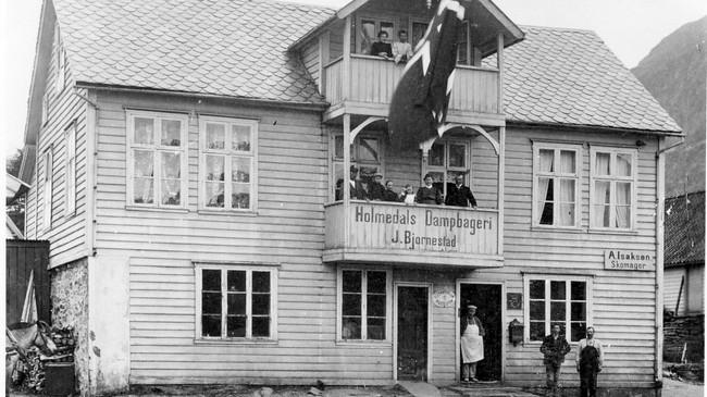 Holmedals Dampbageri i 1910. På huset er det skilt for både post og rikstelefon. I tillegg ser vi at ein skomakar A. Isaksen hadde verkstad i huset. Foto utlånt av Kjell Eikemo.