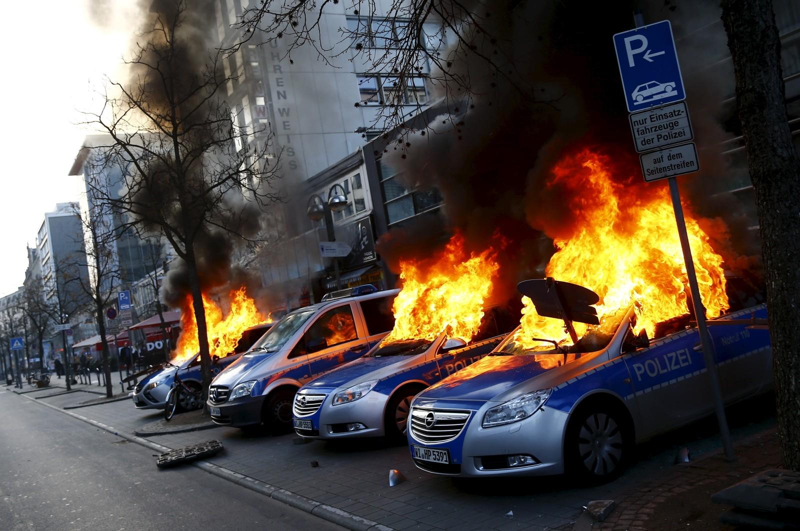 Fire tyske politibiler i brann etter at antikapitalister satte fyr på dem bare timer før åpningen av den europeiske sentralbankens kontorer i Frankfurt, 18. mars.