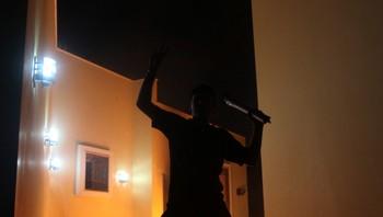 En person strekker hendene i været mens det amerikanske konsulatet i Benghazi står i brann