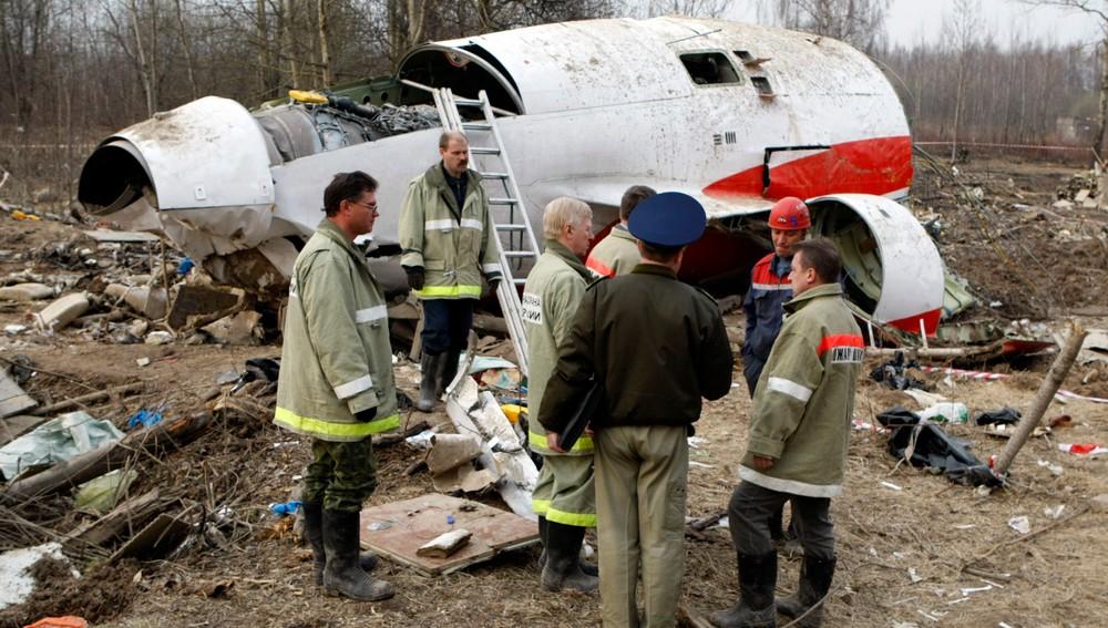 Hjelpearbeidere står ved siden av flyvraket i Smolensk april 2010