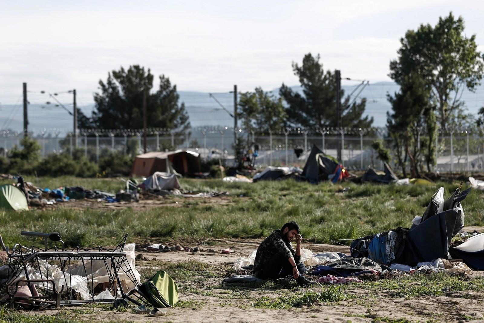 En mann sitter mellom forlatte telt i Idomen. Den provisoriske flyktningleiren på grensa mellom Hellas og Makedonia har husa over 8.400 flyktninger og migranter. Denne uka starta politiet arbeidet med å tømme leiren.