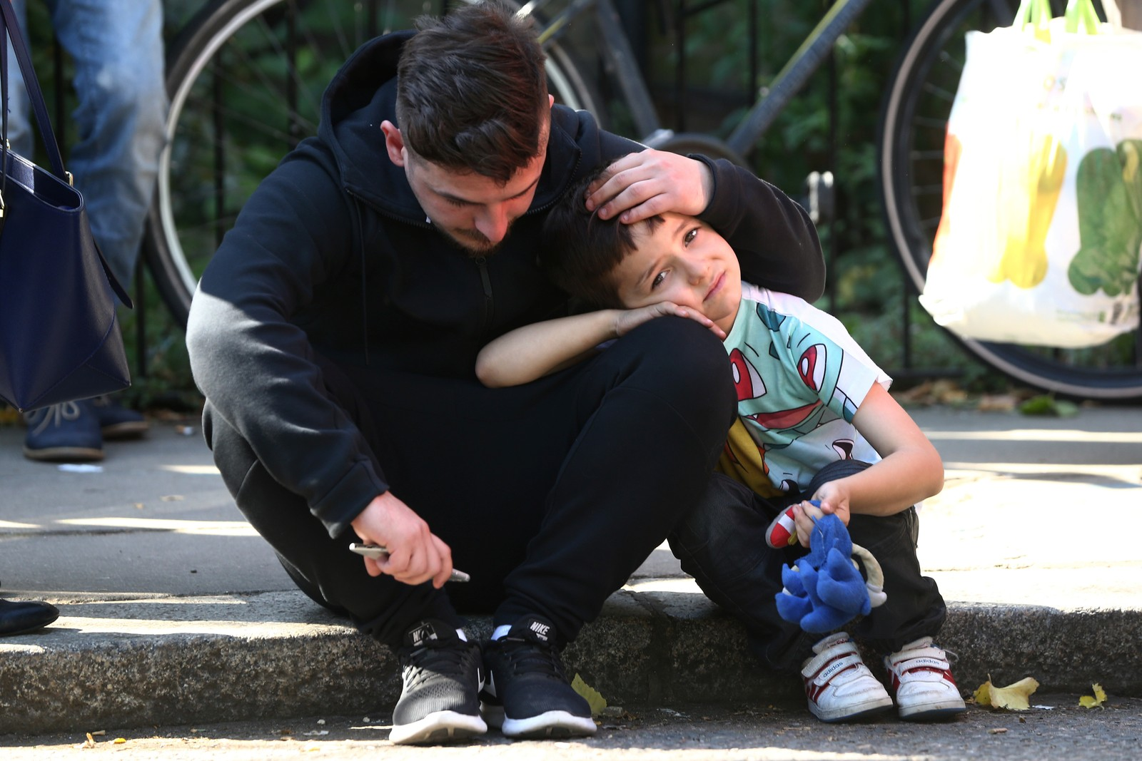 En mann trøster en liten gutt etter den voldsomme brannen som ramma en boligblokk i Grenfell, London denne uka.