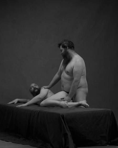 En naken mann med skjegg ligger sidelengs på en seng med rumpa opp. Han ser på en annen naken skjeggete mann som står bak ham med underlivet inntil rumpa og høyre hånd på skulderen hans.