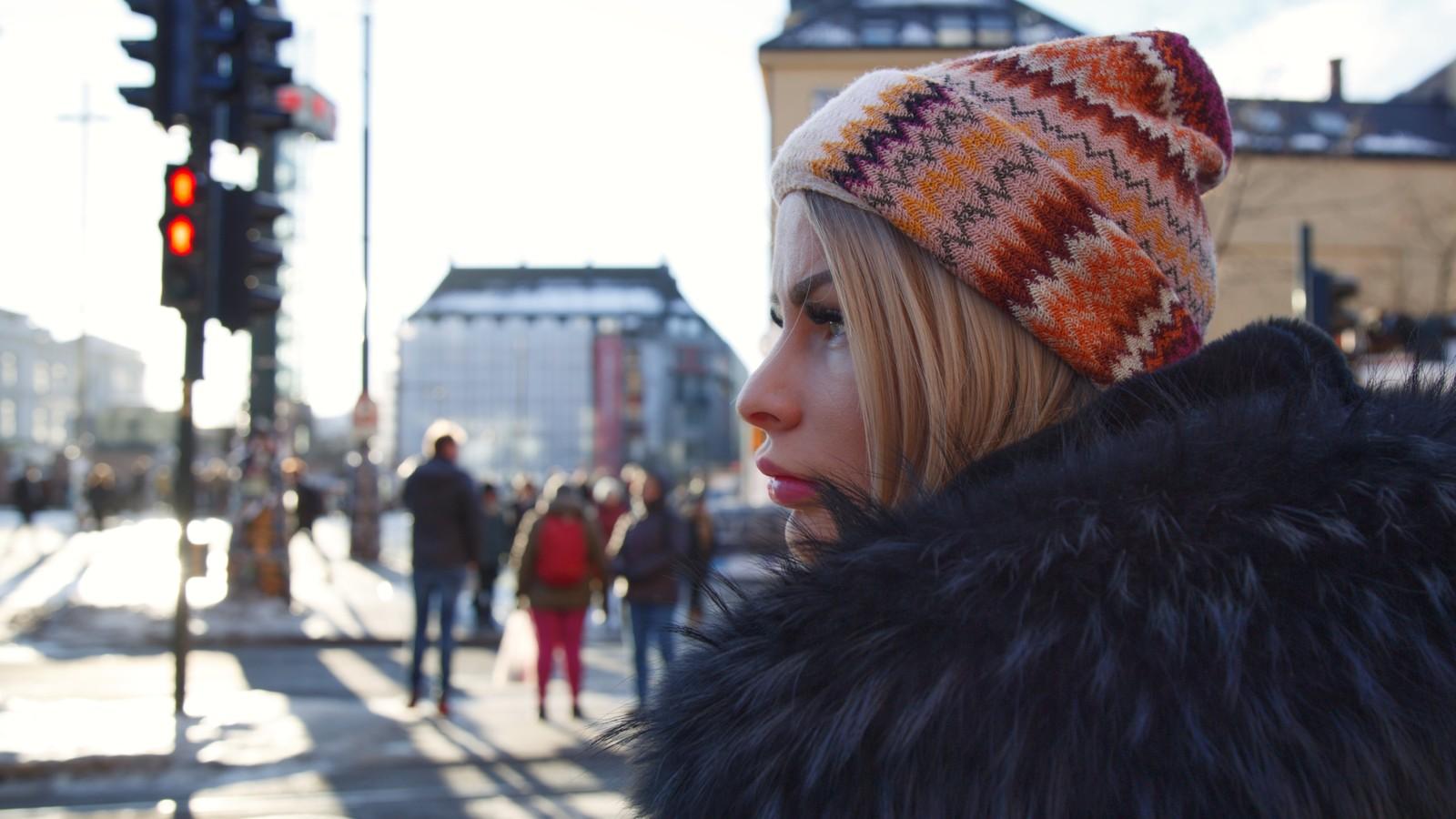Nærbilde av en ung kvinne i profil. Kvinnen har topplue på seg og ser fra høyre mot venstre. Men skimter bygninger og lyskryss i bakgrunnen.